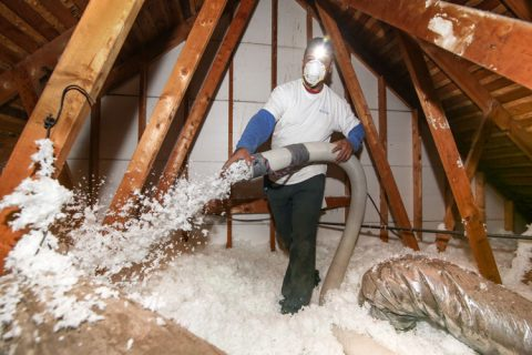 insulation employee in attic blow in insulation